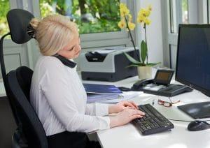 Frau am Computer mit Telefon
