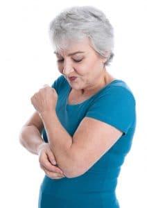 Frau mit Gelenkschmerzen am Ellbogen