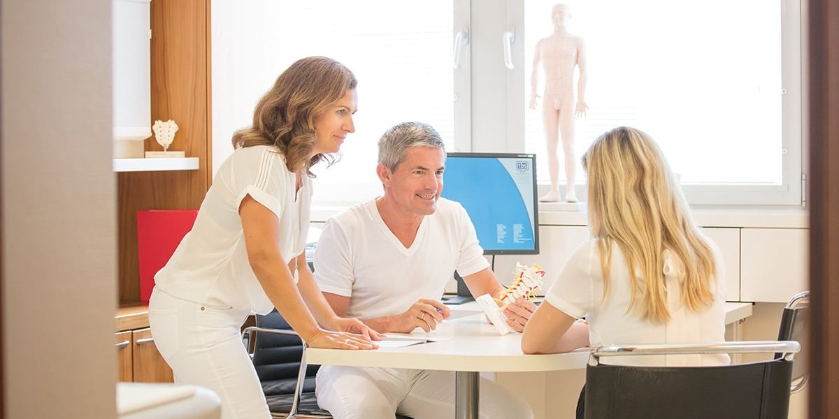 Dr. Schneiderhan zeigt einer Patientin das Modell zum Bandscheibenvorfall